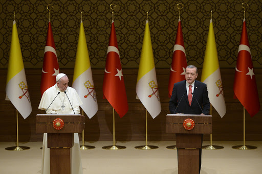 Pope Francis (L) listens to the speech of Turkish President Recep Tayyip Erdogan during their meeting at the presidential palace in Ankara as part of a three day visit in Turkey on November 28, 2014. Pope Francis begins his first visit to Turkey today in a challenging trip aimed at building bridges with Islam and supporting the embattled Christian minorities of the Middle East. The 77-year-old Argentine pope will move to Istanbul on Saturday and Sunday, visiting key sites of the city's Byzantine and Ottoman heritage as well as meeting the Orthodox Ecumenical Patriarch Bartholomew I.  AFP PHOTO / FILIPPO MONTEFORTE