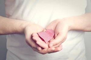 Hombre con corazón de papel en sus manos