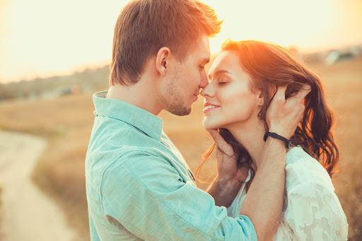 pareja feliz con atardecer de fondo