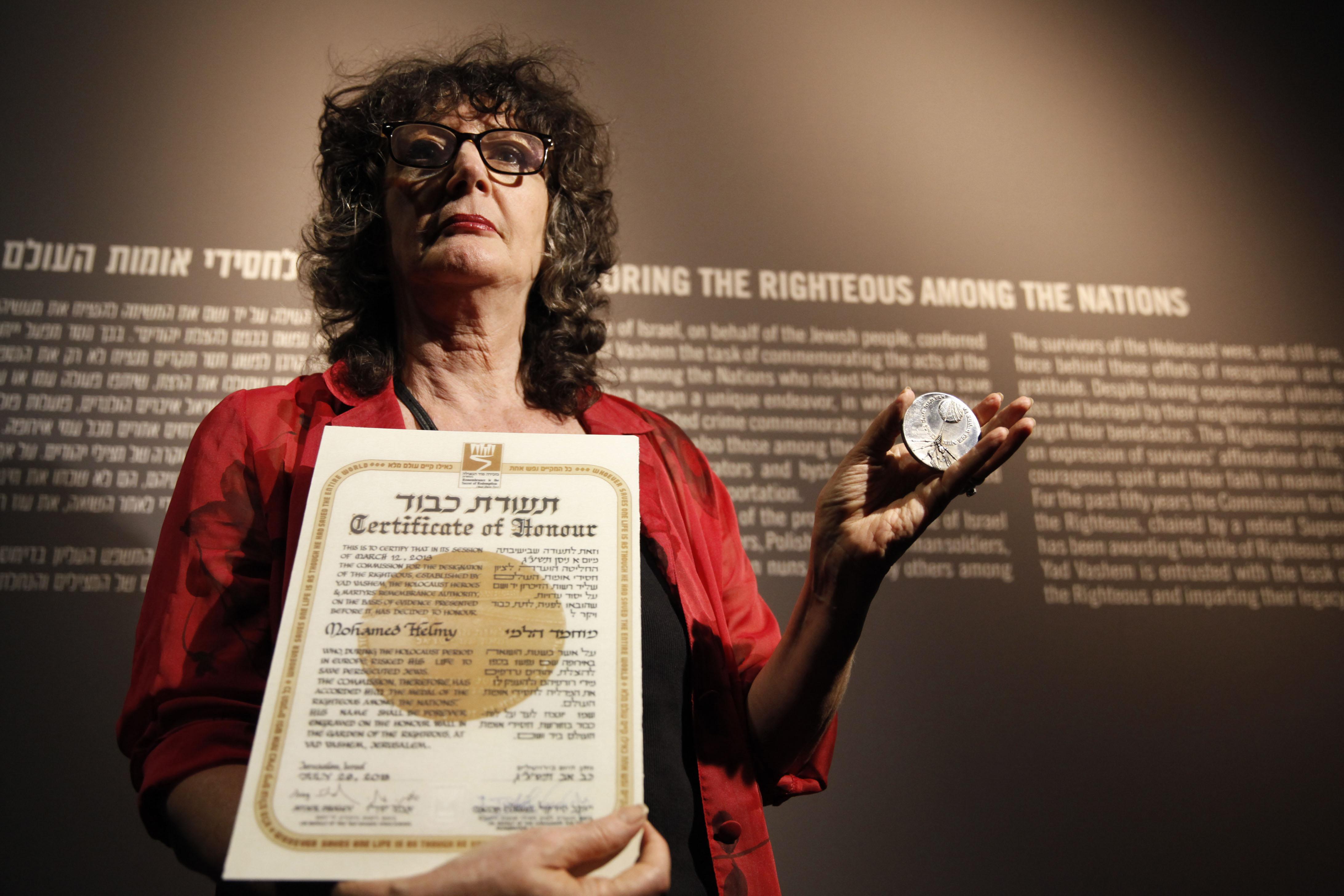 Irene Steinfeldt, directora del departamento de Justos de las Naciones del Yad Vashem, sostiene la medalla y el certificado del dr. Helmy el 30 de septiembre de 2013.  AFP PHOTO / GALI TIBBON / AFP / GALI TIBBON