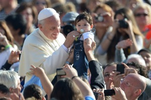 Papa Francisco bendice a un niño en la audiencia general el 16 de octubre.  AFP PHOTO / ALBERTO PIZZOLI
