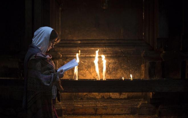 Una mujer reza frente al Santo Sepulcro - EFE