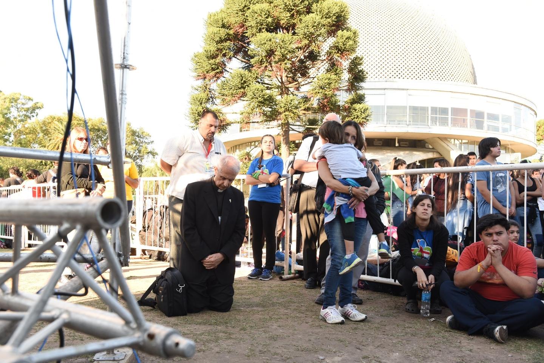 El arzobispo de Buenos Aires, cardenal Mario Poli de rodillas con los jóvenes en el momento de la Adoración Eucarística.
