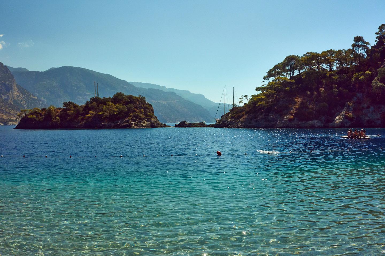 """Abrazada por las montañas circundantes, las aguas de la playa de Ölüdeniz son plácidas como pocas, prácticamente sin oleaje, lo que le ganó el apodo de """"la laguna azul"""""""