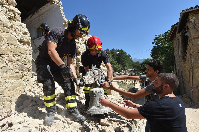 Bomberos recuperan la campana de una de las iglesias en Amatrice / AFP PHOTO / ALBERTO PIZZOLI