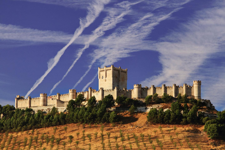 En plena ribera del Duero, el Castillo de Peñafiel vigila desde lo alto lo mismo los viñedos que el pueblo, del siglo X, su famosa Plaza del Coso, y las diecinueve iglesias medievales que dan testimonio de la importancia del lugar.
