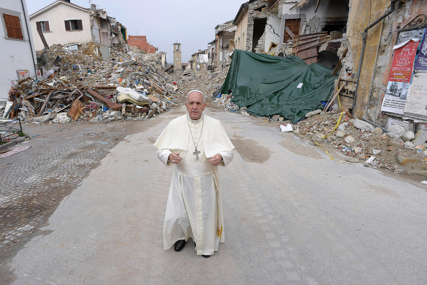 This handout picture released by the Vatican press office on October 4, 2016 shows Pope Francis during a visit in Amatrice, Italy.  Pope Francis on October 4, 2016 made a surprise visit to Amatrice, the small Italian mountain town that bore the brunt of the August 24 earthquake that killed nearly 300 people. The Argentinian pontiff's first point of call was a set of colourful pre-fabricated buildings serving as a makeshift school. Amatrice's school was destroyed in the quake despite having been expensively renovated to make it quake resistant a few years ago.  / AFP PHOTO / OSSERVATORE ROMANO / OSSERVATORE ROMANO