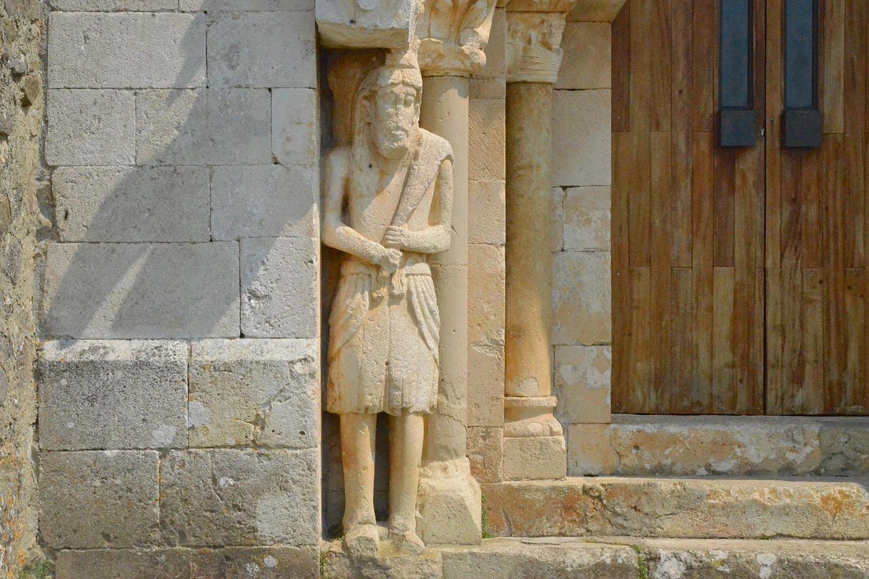 Una enorme figura barbuda –única en el románico– parece llevar un saco a la espalda, mientras que por ventanitas asoman cabezas enigmáticas (quizá ermitaños emparedados en vida, algo corriente en el Camino de Santiago)