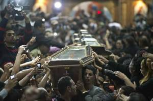 Egyptian Copts carry four coffins down the aisle of the Virgin Mary Coptic Christian church in Cairo's working class neighbourhood of Al-
