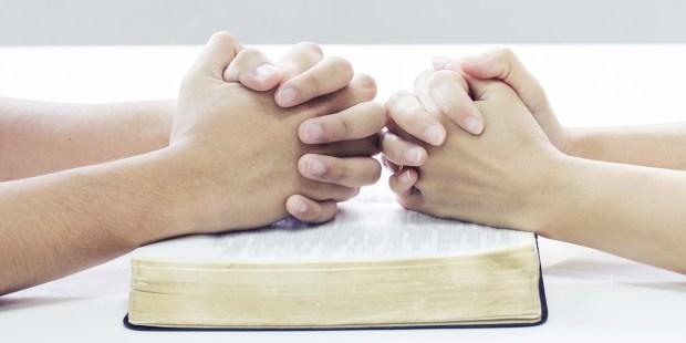 COUPLE QUI PRIE AU DESSUS D'UNE BIBLE