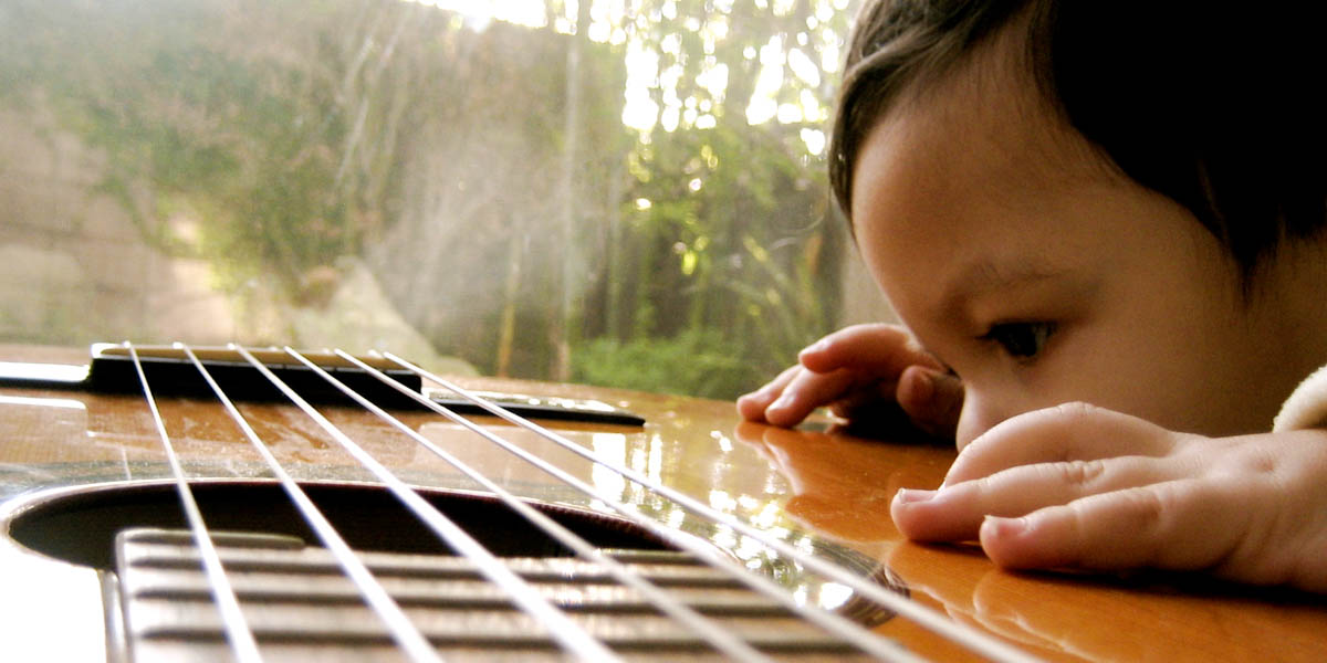 CHILD LOOKING AT GUITAR