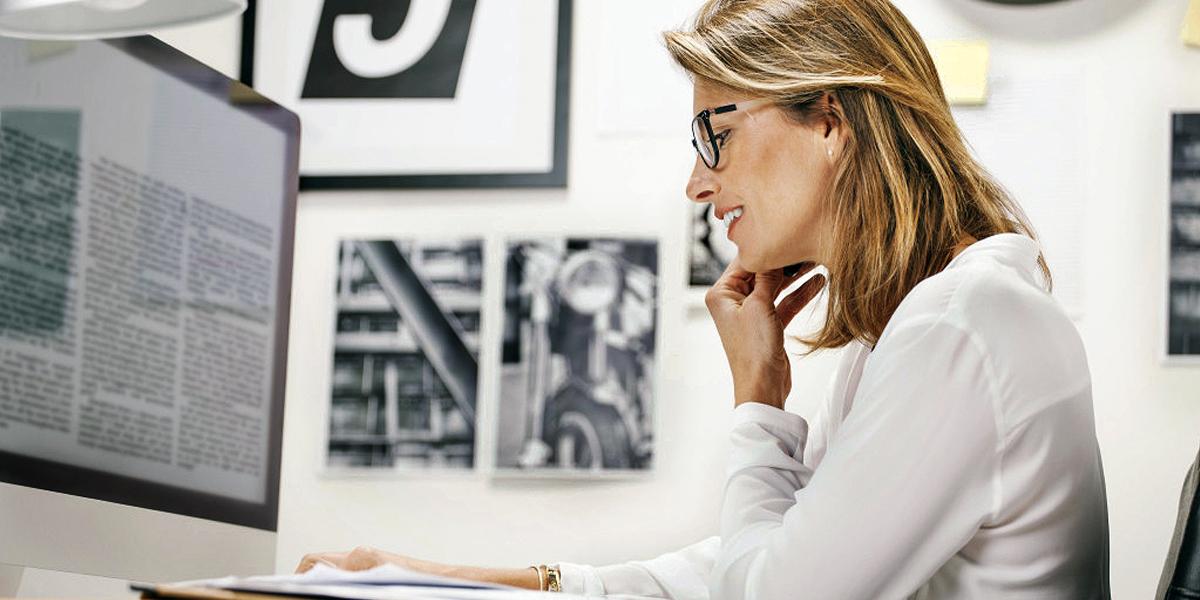 Młoda kobieta w biurze przy biurku przed komputerem rozmawia przez telefon
