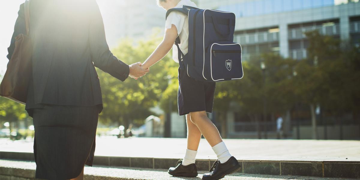 Mama trzymająca za rękę syna idącego po murku w stroju szkolnym