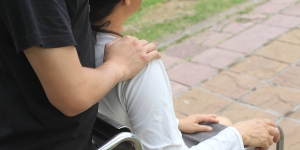 MAN HELPING DISABLED WOMAN