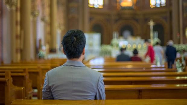 ASIAN MAN PRAYING IN CHURCH