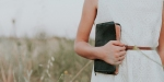 WOMAN,HOLDING,BIBLE,FIELD