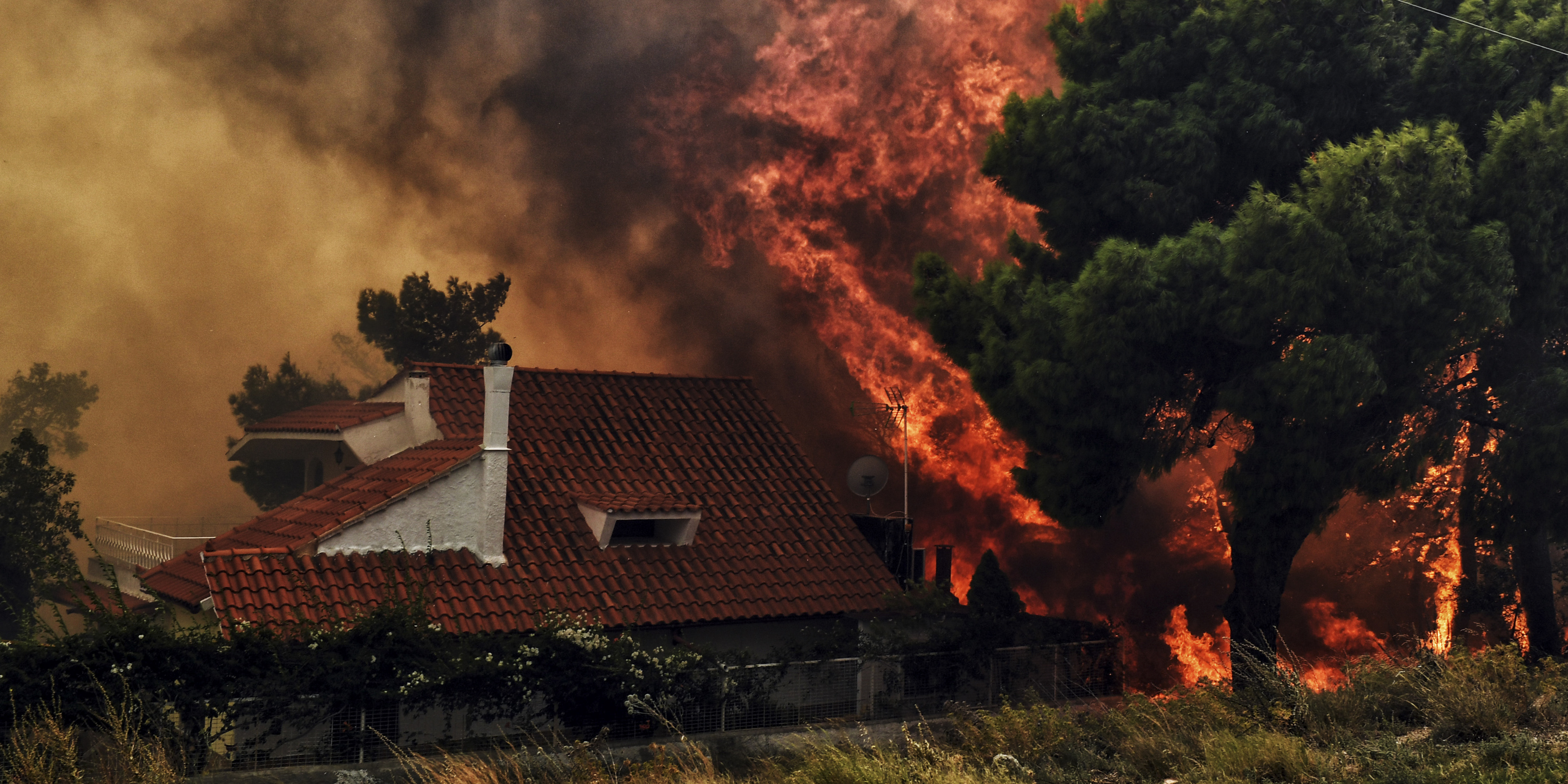 "A house is threatened by a huge blaze during a wildfire in Kineta, near Athens, on July 23, 2018. More than 300 firefighters, five aircraft and two helicopters have been mobilised to tackle the ""extremely difficult"" situation due to strong gusts of wind, Athens fire chief Achille Tzouvaras said. / AFP PHOTO / VALERIE GACHE"