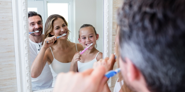 Parents and daughter brushing their teeth