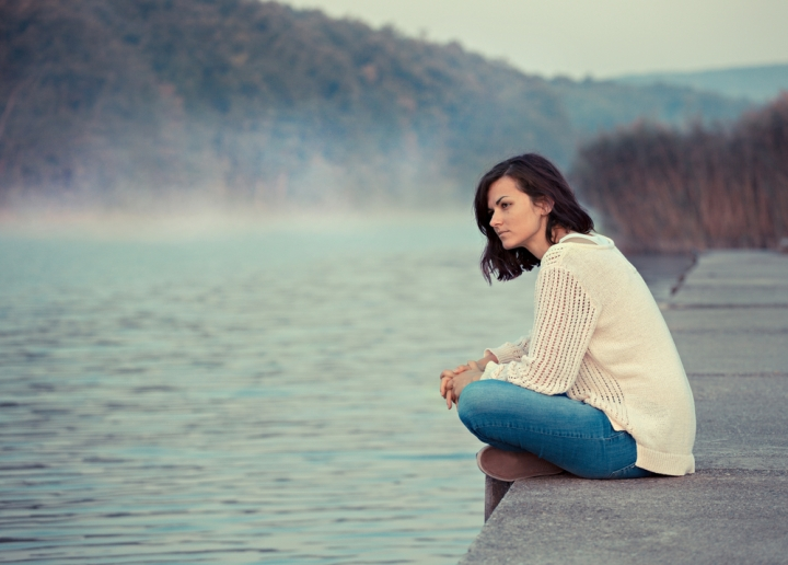 GIRL SITTING BY LAKE