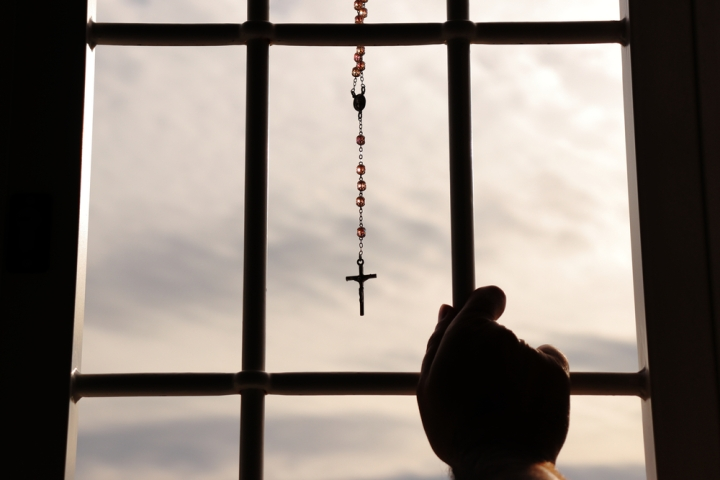 Religious rosary hanging on window with grate